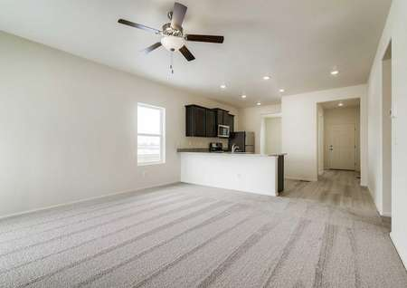 Interior photo of a spacious living room with carpet and ceiling fan and adjacent kitchen with breakfast bar and dark brown cabinets.