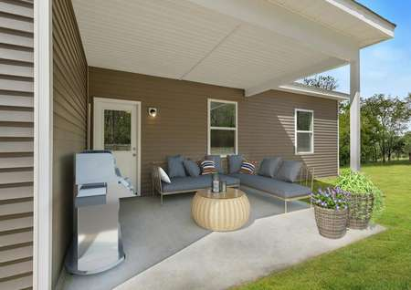 Decorated covered back patio with stainless grill, wicker coffee table, wicker planters, sectional loungers with gray cushions and striped pillows on home with dark gray home with white trim.