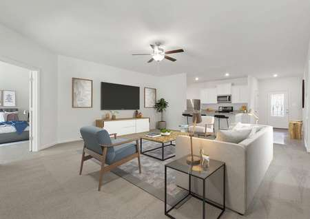 Staged living room with white sofa, gray armchair, coffee and end table, TV on wall and entertainment cabinet beneath it, ceiling fan, view into master bedroom, view into kitchen and foyer.