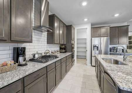Mead new home kitchen with grey granite, brown cabinetry, and recessed lights