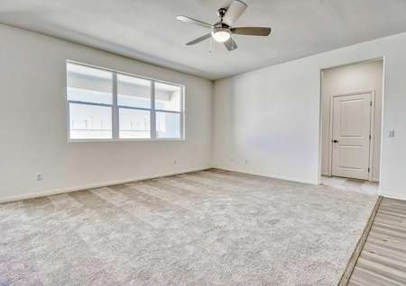 The living room in the Rosebud floor plan with carpet floors, three windows and a view of the front door.