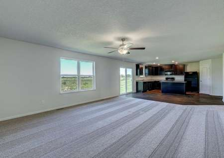 Pennington new home with gray carpeting, overhead ceiling fan, and wood floors in the kitchen