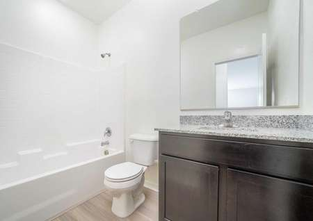 Balboa bathroom with brown cabinets, large vanity mirror, and white fixtures