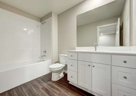 The secondary bathroom in the Kennedy floor plan with a bathtub/shower combo, vinyl wood floors and marble countertops.