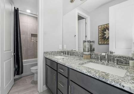 Mead bathroom with two sinks, granite countertop, and private toilet/bath room