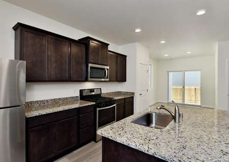 Kitchen with dark brown cabinets, stainless appliances and speckled gray granite, recessed lights and stainless single basin sink.