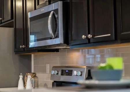 Model home kitchen completed with stainless steel microwave and oven, modern wooden cabinets, and decor on the countertop