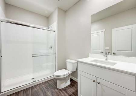 The Crystal floor plan secondary bathroom with a walk-in shower, a sink, cultured marble countertops and white cabinets.