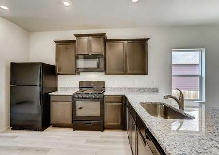 Shavano kitchen with light color granite, undermount sink with modern faucet, and dark brown cabinets