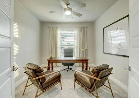 Staged home office with brown desk and brown chairs.
