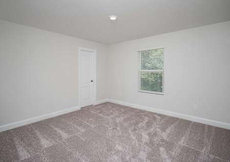Carpeted secondary room of the Kiawah floor plan with a closet, white wallsand a single hung window covered by blinds.