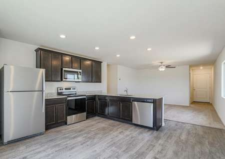 Open kitchen with stainless steel appliances and dark cabinets.