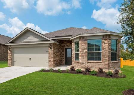The exterior of the Texoma floor plan that is made of brickwith a lush green grass yard and a two-car garage.