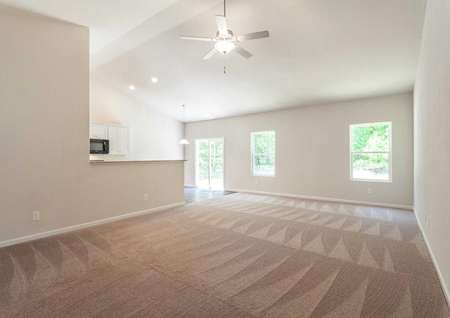 Alexander great room with brown carpet, vaulted ceilings, and white trim