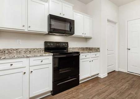 Alamance kitchen with speckled granite counters, wood floors, and white cabinetry