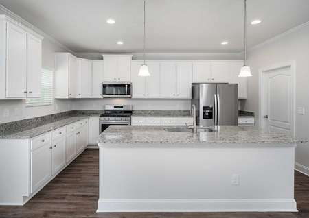 Kiawah floor plans kitchen with an island, granite countertops, white cabinet hardwareand a side by side refrigerator.