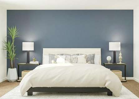 Rendering of owners bedroom with large   bed, blue accent wall and dual side tables, adjacent to bathroom.