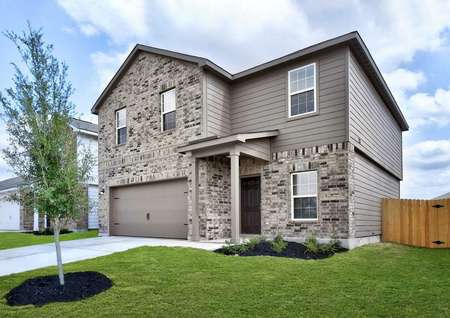 Rio new home completed with light brick siding, green grass and tree landscaped yard, and two living levels