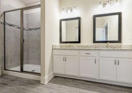 Double sinks, granite countertops and a step-in shower are located in the full bathroom of the owner's retreat.