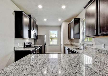 Jasper kitchen with gray granite counters, dark brown cabinets, and recessed lights