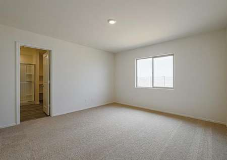 Spacious master bedroom with tan carpet and large windows.