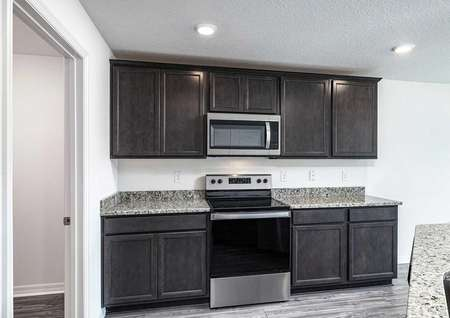 Stainless steel appliances next to granite countertops and tall, upper-wood cabinets.