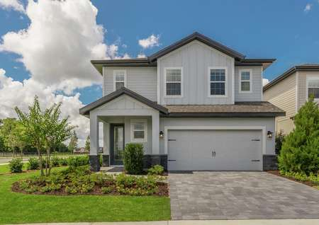 Exterior of two-story home with siding, a two-car garage and beautiful front yard landscaping.