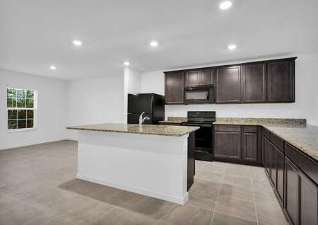 A kitchen island with granite counter tops and a sink in the St. Martin floor plan.