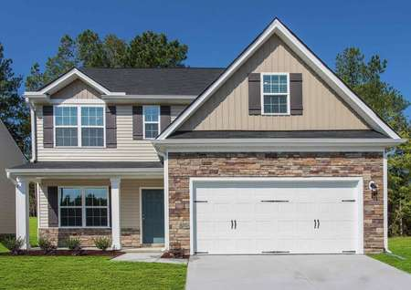 Hartford house plan street view with two-car garage, brown shutters, and landscaped yard