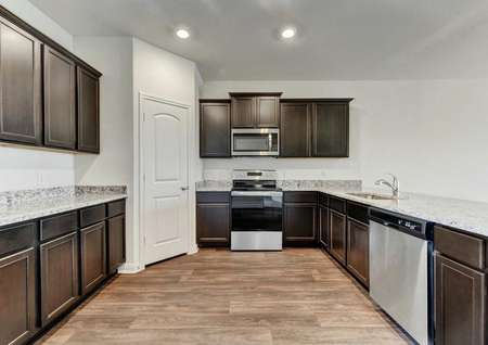 Travis kitchen with stainless steel appliances, granite countertops and wood-look flooring