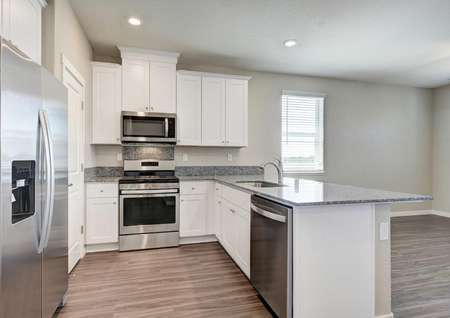 The Crystal floor plan kitchen with wood-like floors, stainless steel appliances and granite countertops.