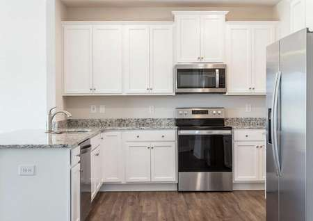 Allatoona kitchen with stainless steel fridge, oven, and microwave on white finish