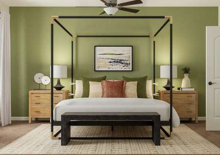 Rendering of the spacious master suite in   the Roanoke floor plan. The room has a window and ceiling fan and is   decorated with a poster bed, two nightstands, a bench at the end of the bed   and a rug.
