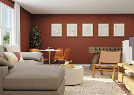 Rendering of the upstairs loft decorated   with a gray couch and tv, a table with four chairs and a foosball table.