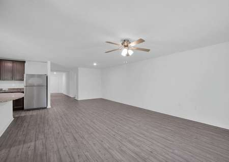 Sizable family room with a ceiling fan and luxury vinyl plank flooring.