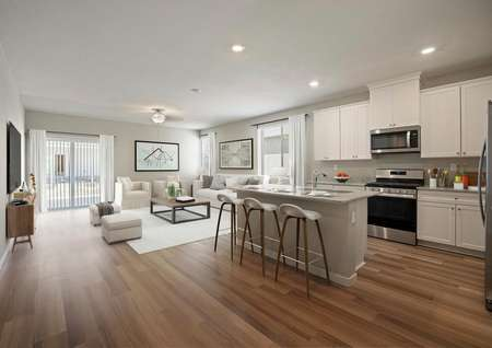Staged home with an open layout featuring white cabinetry in the kitchen and a bright living room.