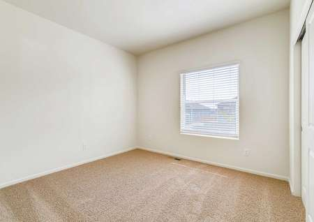 Pike model home carpeted bedroom with a window.