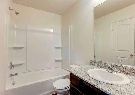 Aitkin bathroom with granite countertop, light fixtures, and large vanity mirror