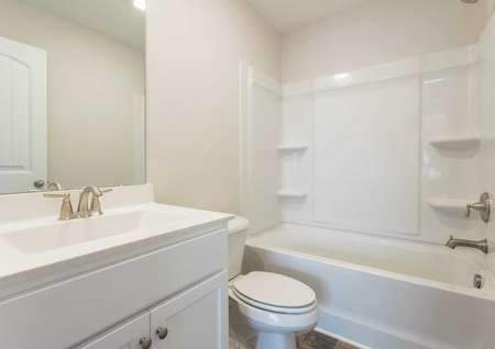 Avery guest bathroom with white appliances, large mirror, and bathtub/shower fixture