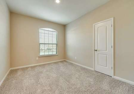 Bedroom with tan walls, white trim and brown carpet.