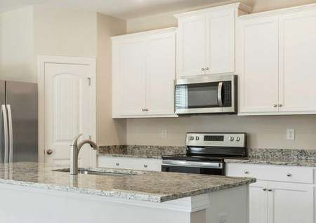 Avery kitchen with granite counters, modern appliances, and white cabinets
