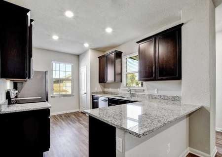 Jasper finished kitchen with brown cabinets, gray granite counters, and can lights