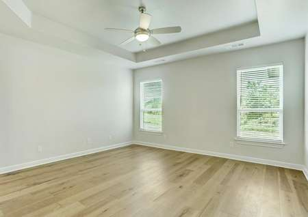 The master suite of the Mantle plan has gorgeous wood floors and a ceiling fan.