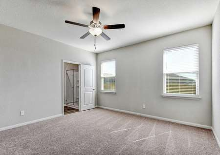 Jasper master bedroom with carpeted floors, gray walls with white trim, and access to private bathroom