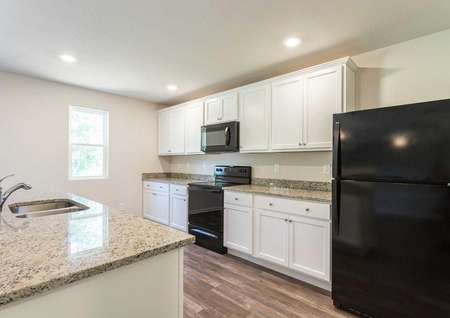 Madison kitchen with black refrigerator, granite countertops, and island sink