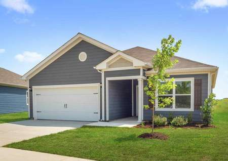 Exterior view of the Blanco model home with grey siding, white trim, shingle roofing, white 2 car garageand professionally landscaped front yard