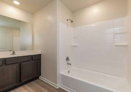 Sabine bathroom with white shower and bathtub unit, brown cabinet, and white vanity top