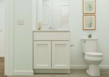 Rendering of the full bath showing the   white cabinet vanity adjacent to the toilet. Decorative artwork of plants   hang above the toilet.