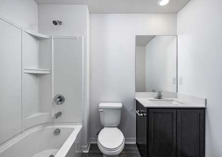 The spare bedroom features its own full bathroom with a bathtub, toilet and sink.