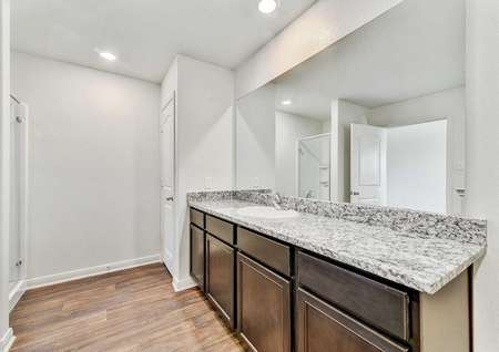 Rio bathroom with granite countertops, extended glass mirror, and white fixtures